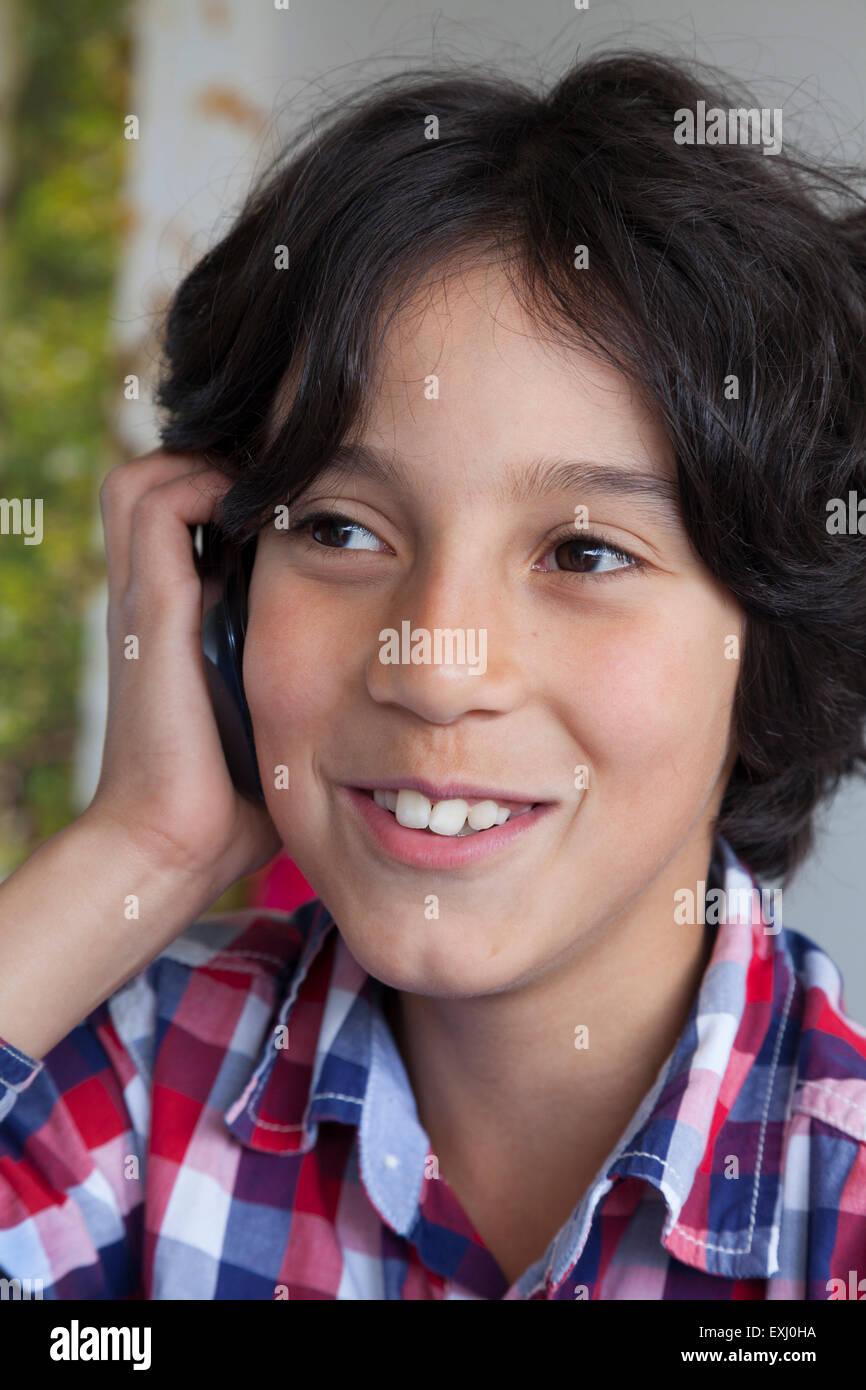 Sorridente ragazzo adolescente con il suo telefono cellulare Immagini Stock