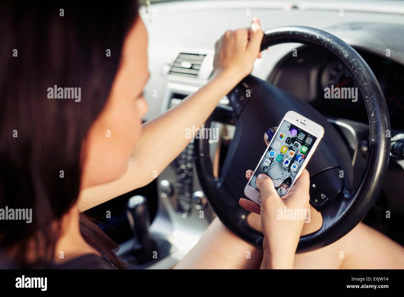 Donna che utilizza il telefono cellulare durante la guida Immagini Stock