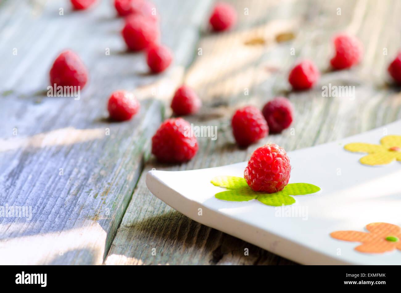 Rasberries sulle moderne piastra bianca isolata su uno sfondo di legno Immagini Stock