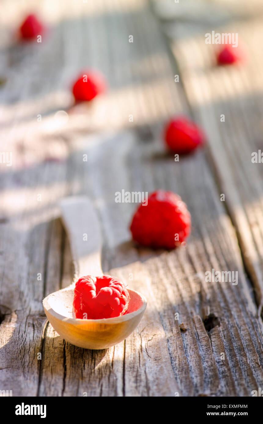 Rasberry in cucchiaio di legno isolato su vintage sfondo di legno Immagini Stock