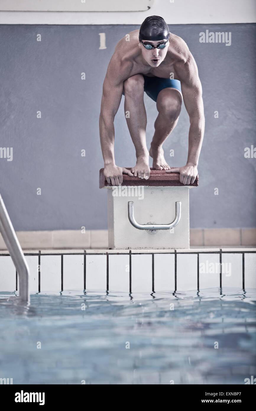 Nuotatore nella piscina coperta in posizione di partenza Immagini Stock
