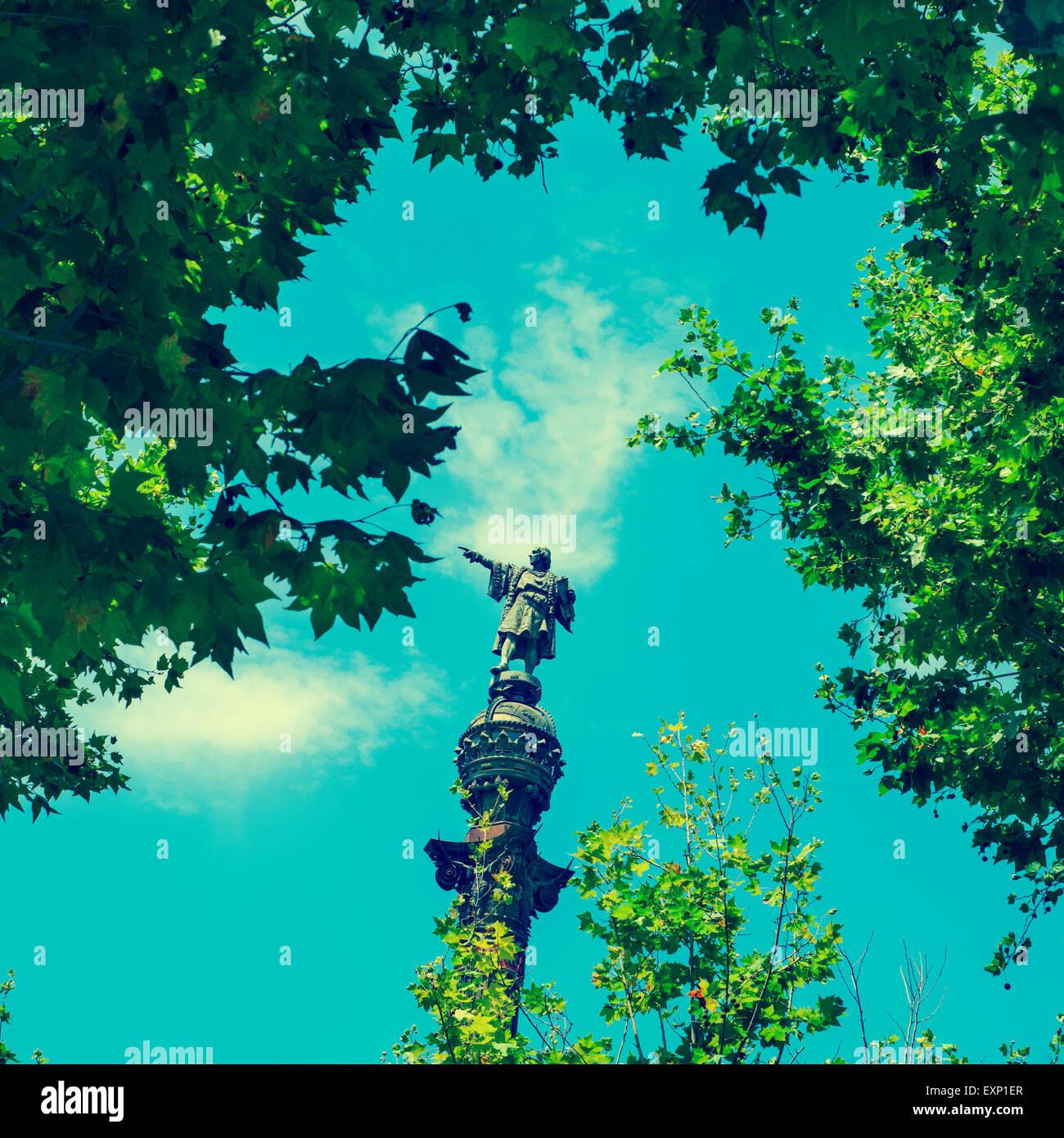 Una vista del monumento di Colombo a Barcellona, Spagna, tra alcuni alberi, con un effetto retrò Immagini Stock