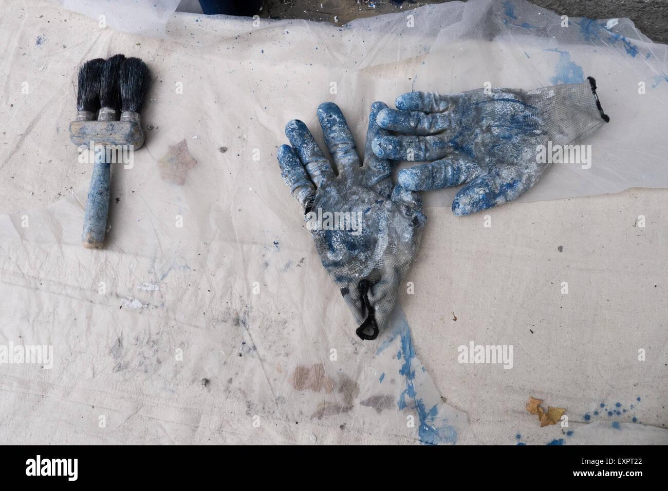 A Notting Hill, Londra, Inghilterra. Coppia di operaio di guanti e pennello su un foglio di plastica. Immagini Stock