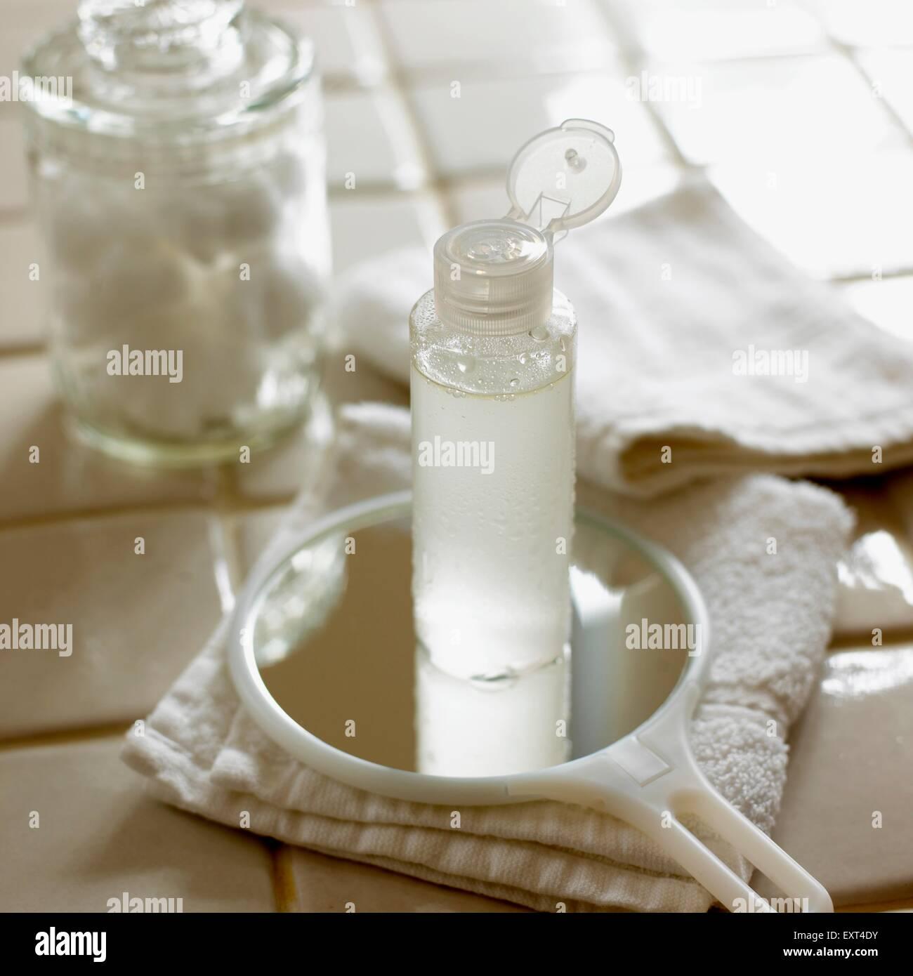 Bottiglia di aloe e lavanda toner, una mano specchio, Salvietta ripiegata, di flanella, e vaso di lana di cotone Foto Stock