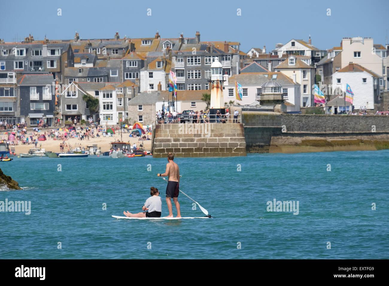 St Ives, Cornwall, Regno Unito: giovane su Paddleboard con St Ives in background. Immagini Stock