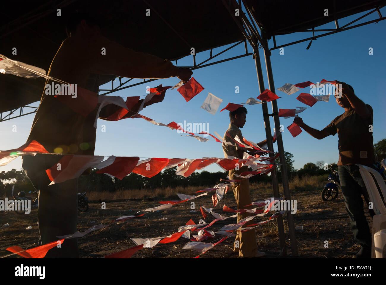 Persone appendere fuori indonesiano bandiere di piccole dimensioni per un evento locale. Immagini Stock