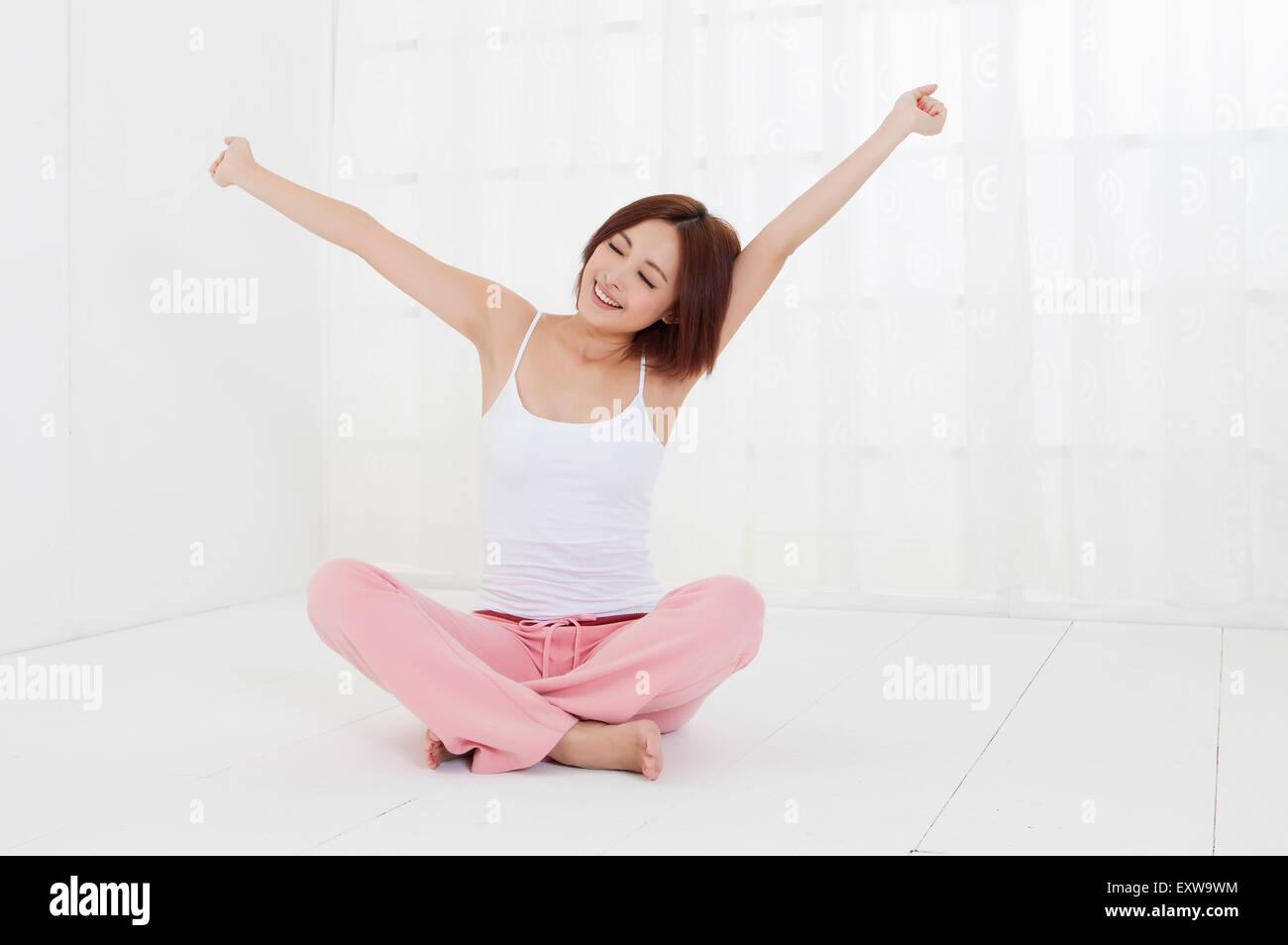 Giovane donna seduta sul pavimento con le braccia aperte, Immagini Stock