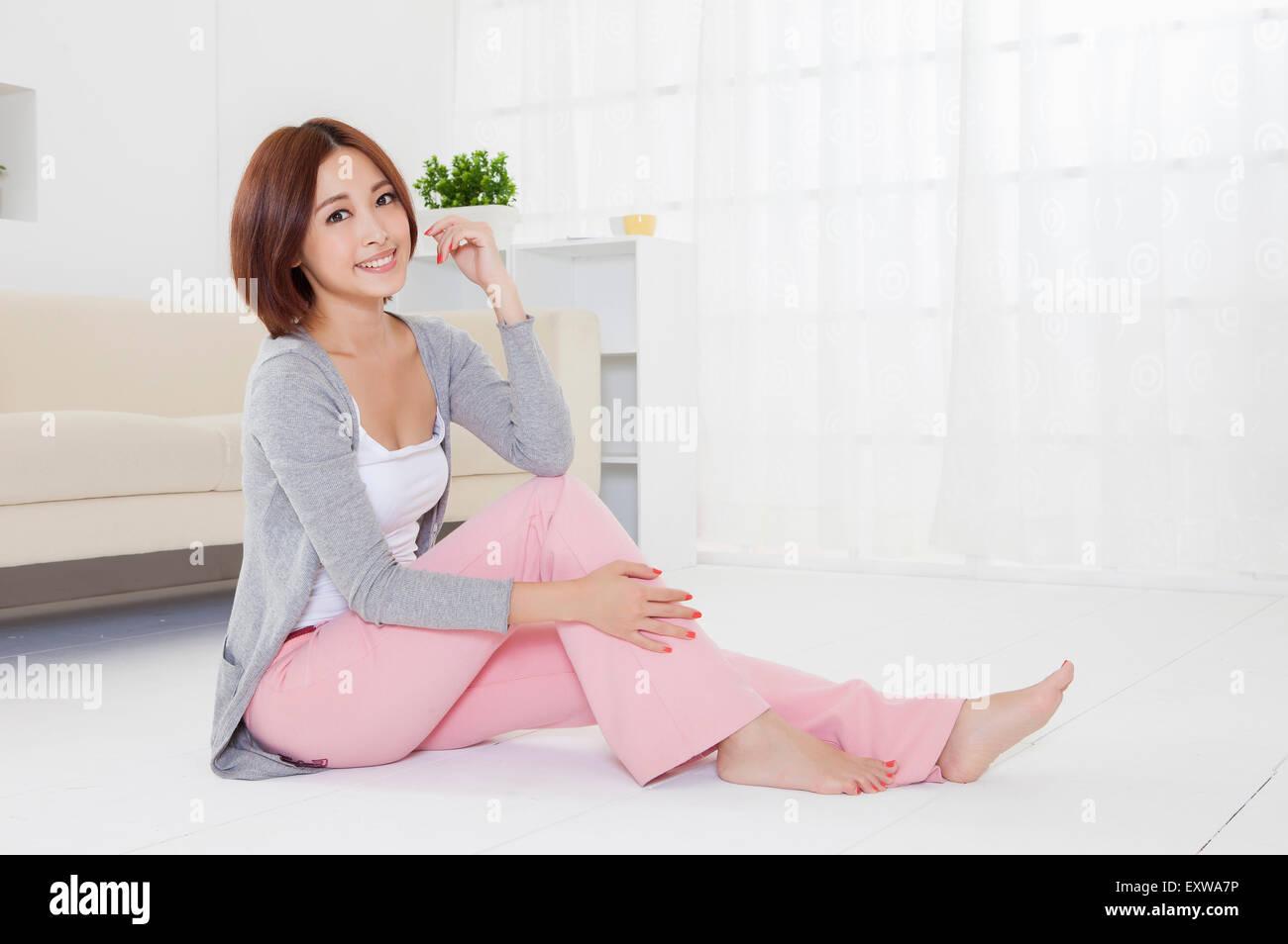 Giovane donna seduta sul pavimento e sorridente alla telecamera, Immagini Stock