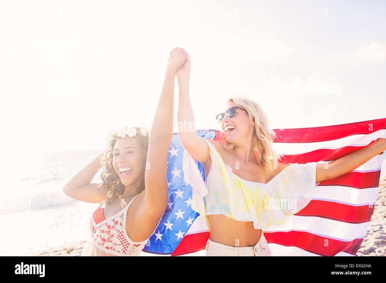 Amici di sesso femminile sulla spiaggia con bandiera americana Immagini Stock