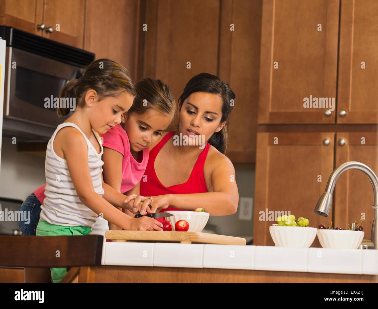 Madre e bambini (6-7, 8-9) preparare il cibo in cucina Immagini Stock
