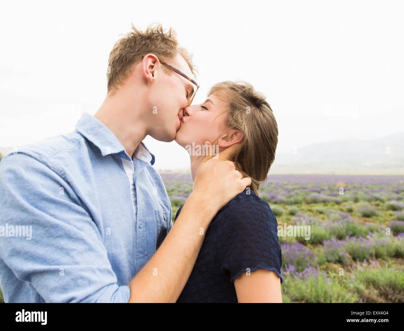 Coppia giovane baciare con campo sullo sfondo Immagini Stock