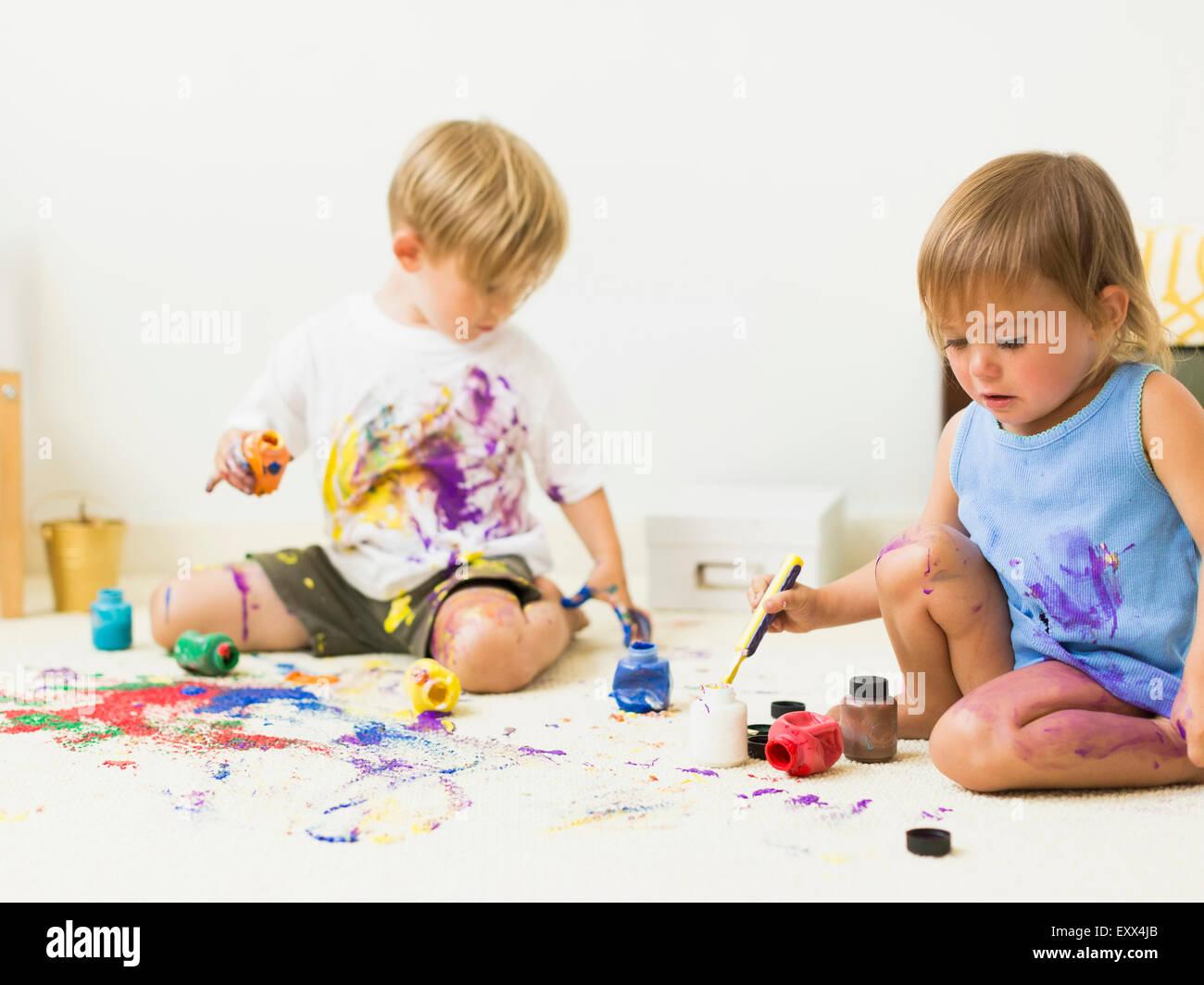 Bambini (2-3) pittura su un tappeto Immagini Stock