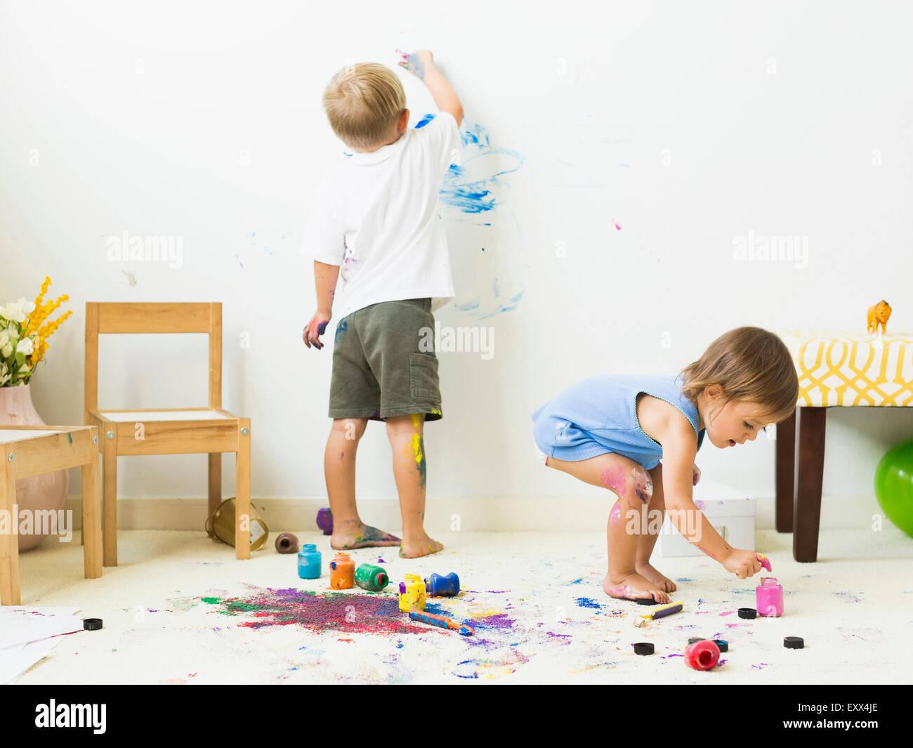Bambini (2-3) dipinto sul tappeto e la parete Immagini Stock