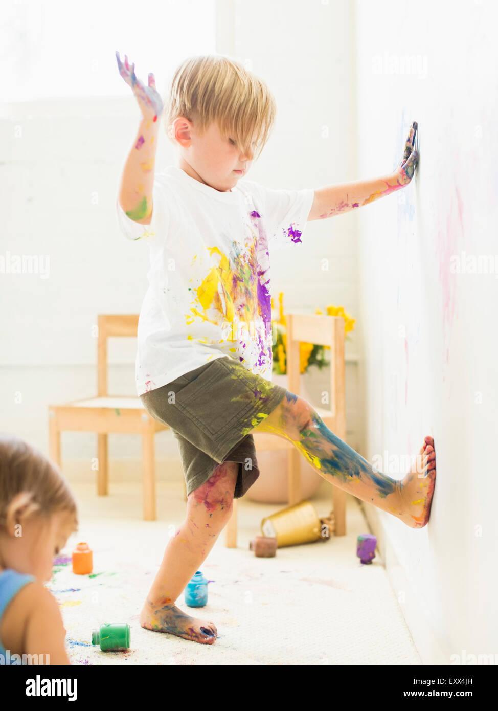 Ragazzo (2-3) dipinto sul muro con le mani e gambe Foto Stock