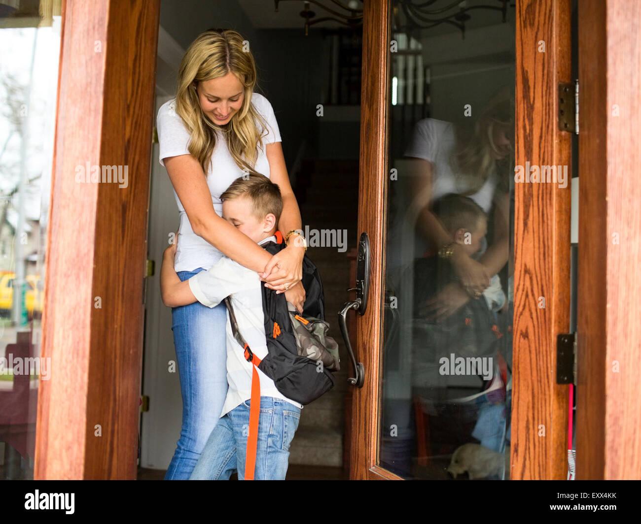 Ragazzo (6-7) abbracciando la madre prima di partire per la scuola Immagini Stock