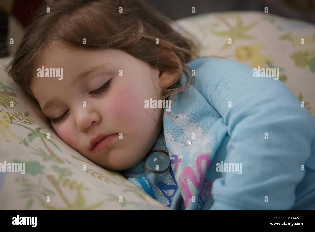 Ragazza dorme nel letto Immagini Stock