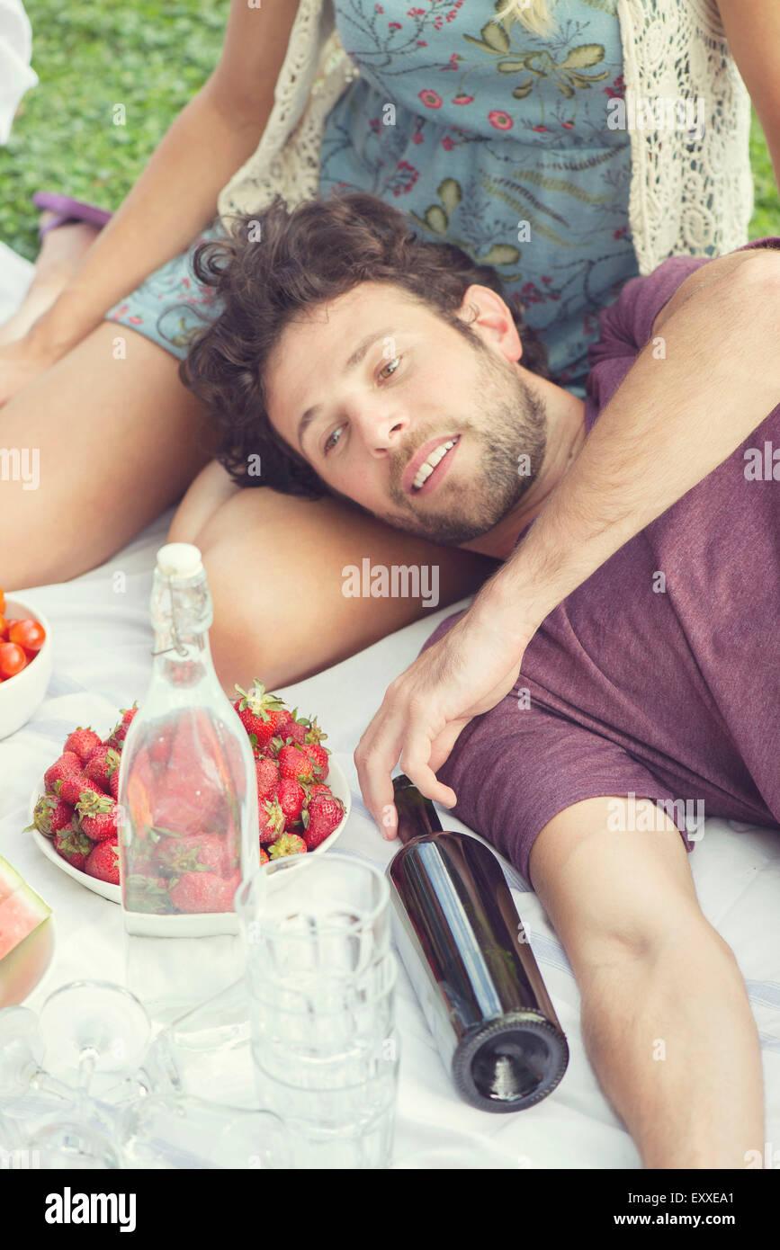 L'uomo rilassante con il compagno a picnic Immagini Stock