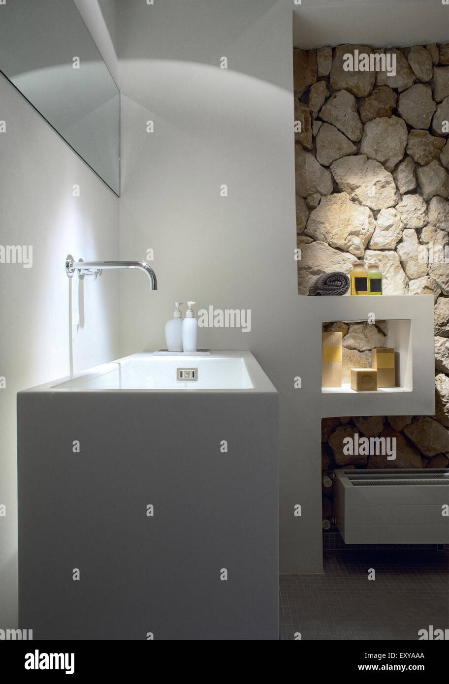 In primo piano del lavandino in bagno moderno la cui parete è rivestita con pietra Foto ...