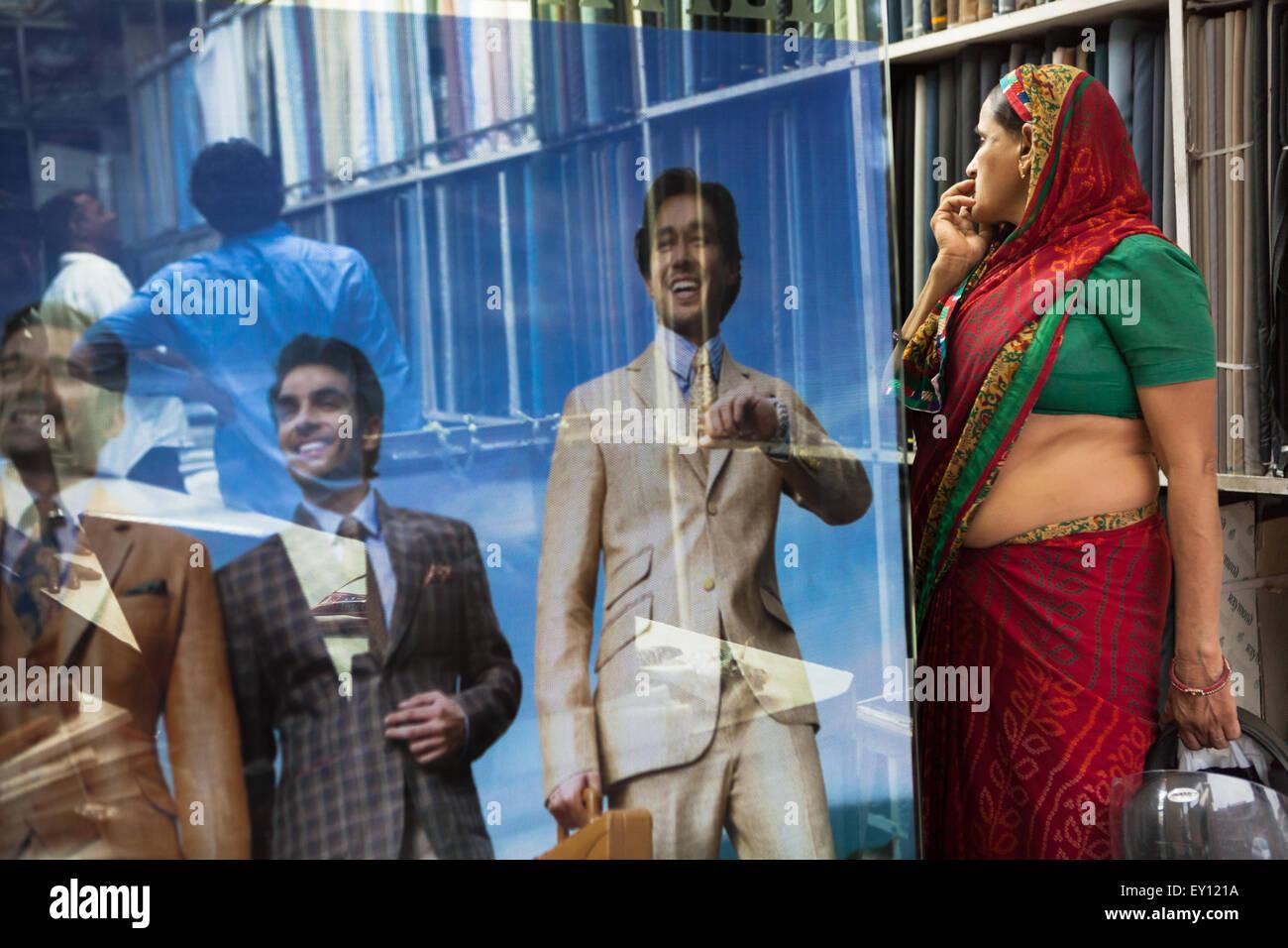 Una donna che indossa tradizionale sari sorge in un moderno uomini negozio di abbigliamento a Jaipur, India. © Immagini Stock