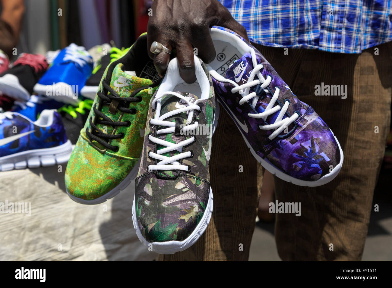 Uomo di vendita o replica fake Nike scarpe da ginnastica in un mercato di  Catania a8f2d473b45