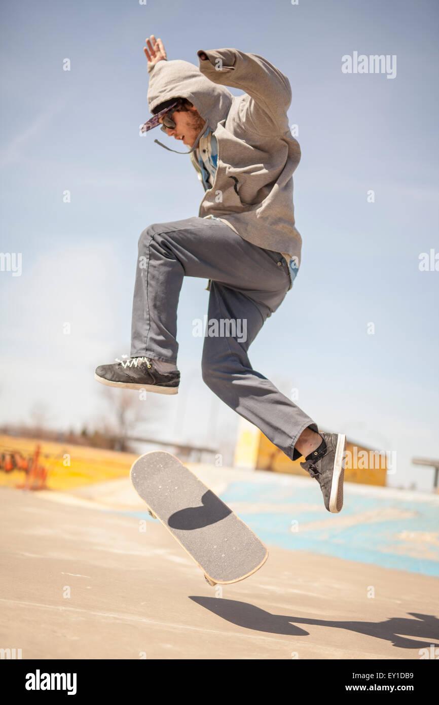 Giovane appassionato di skateboard in skatepark durante il giorno Foto Stock