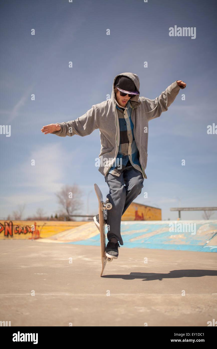 Giovane appassionato di skateboard in skatepark facendo vecchia scuola trucchi Immagini Stock