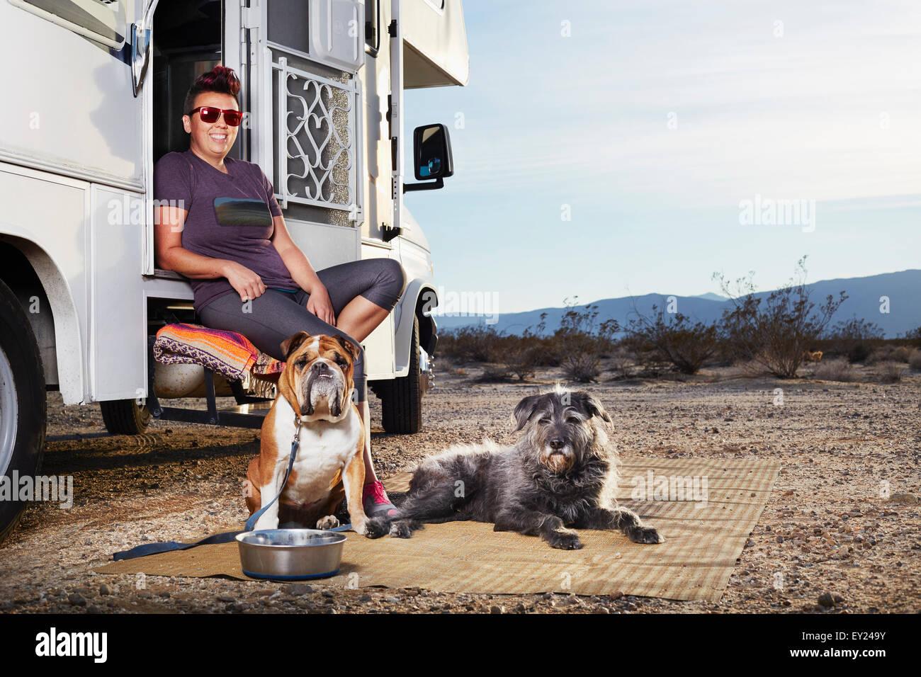 Ritratto di metà donna adulta e due cani seduti sul camper passo, Borrego Springs, California, Stati Uniti Immagini Stock