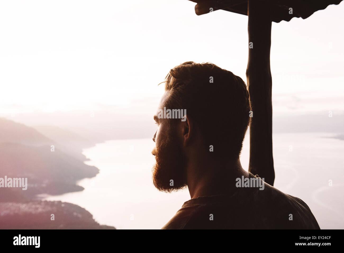 Uomo che guarda fuori dal naso indiano, il lago Atitlan, Guatemala Immagini Stock