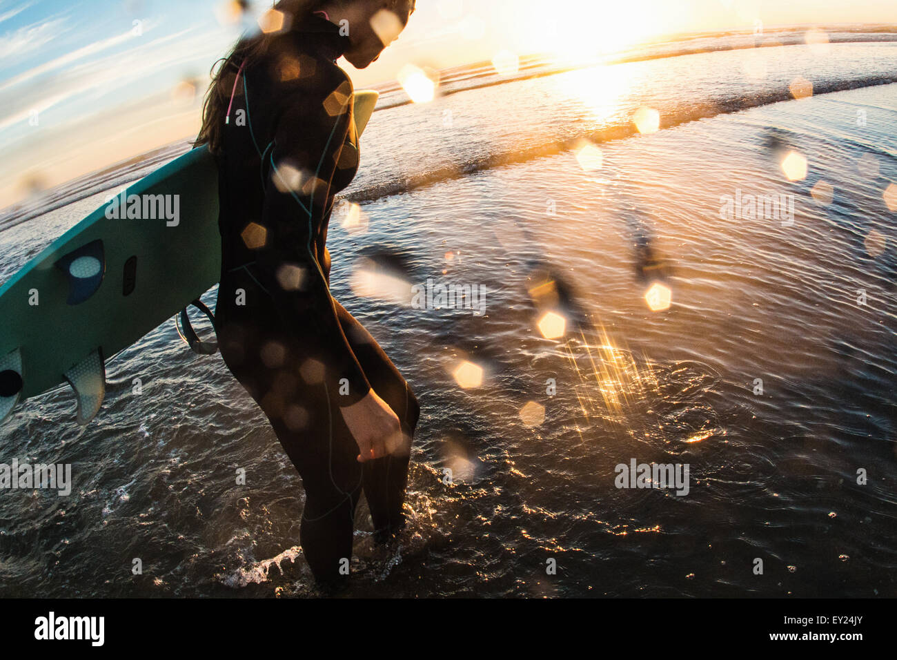 Surfista femmina paddling in mare al tramonto, Cardiff-By-The-Sea, CALIFORNIA, STATI UNITI D'AMERICA Immagini Stock