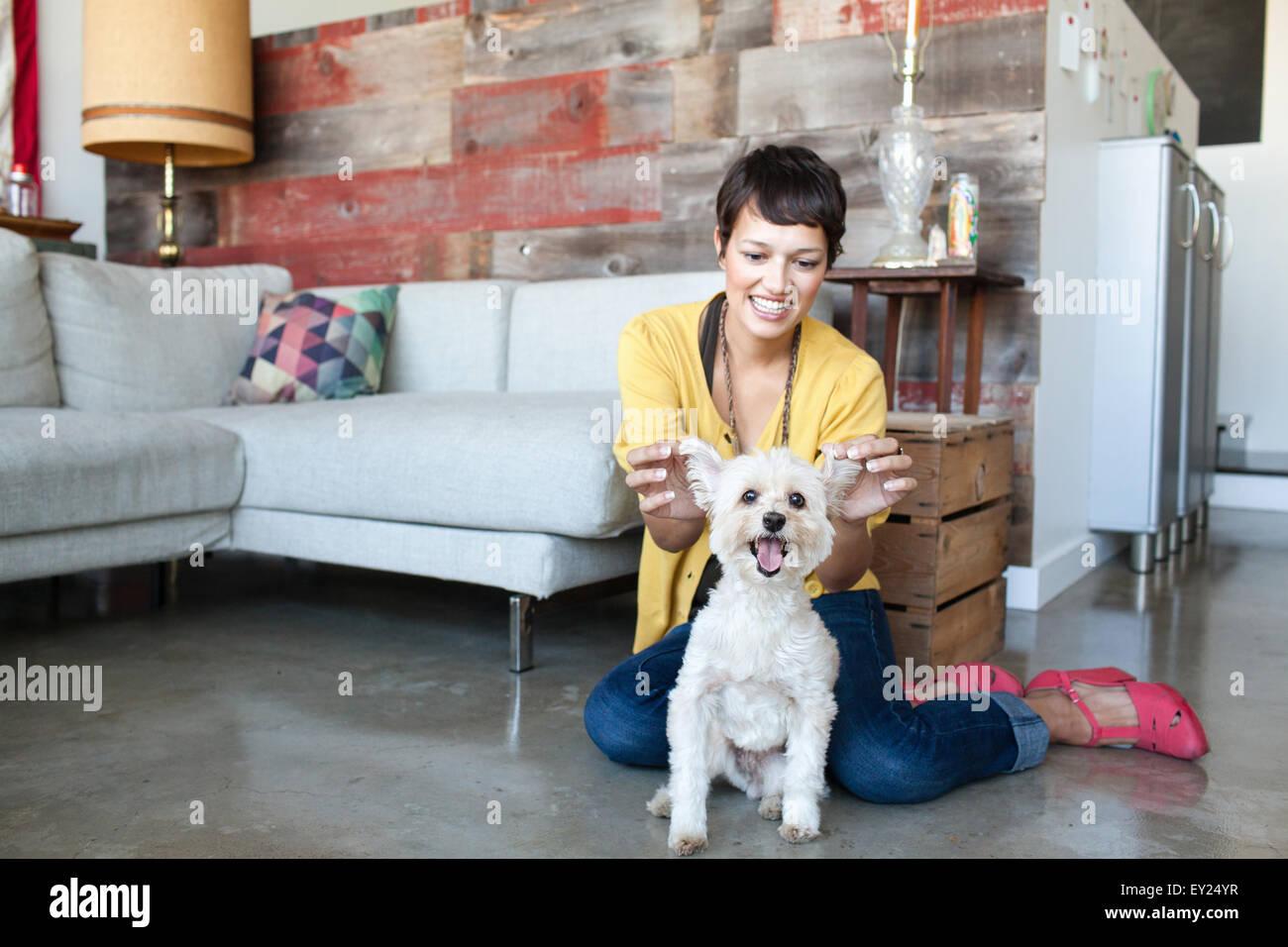 Giovane donna azienda fino alle orecchie dei cani in salotto Immagini Stock