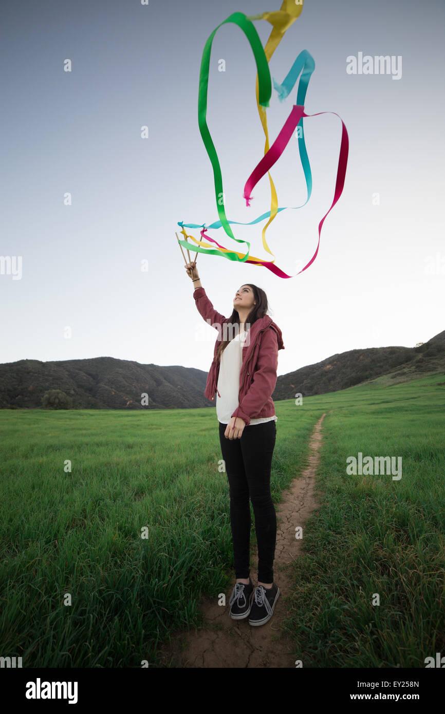 Giovane donna in piedi in campo tenendo su nastri di danza Immagini Stock
