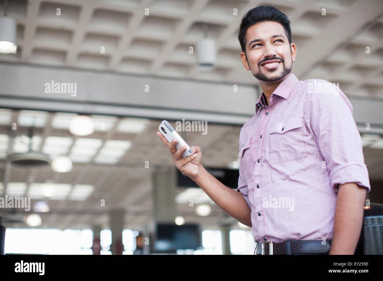 Basso angolo vista del giovane uomo utilizza lo smartphone in una stazione ferroviaria Immagini Stock