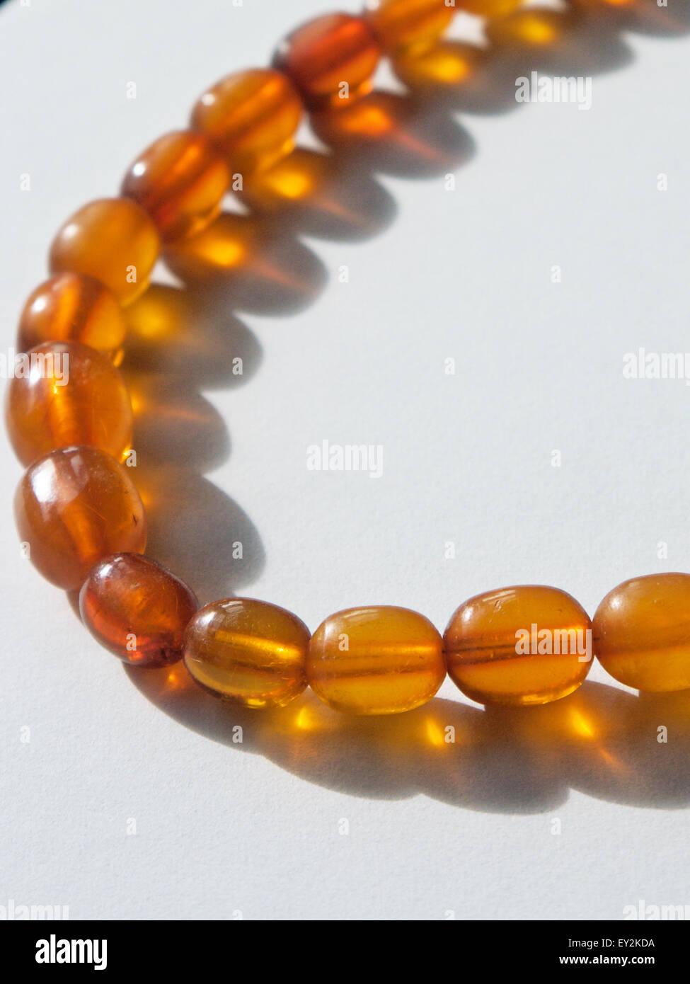 Girato a tenuta di un ambra, collana di perle. Immagini Stock