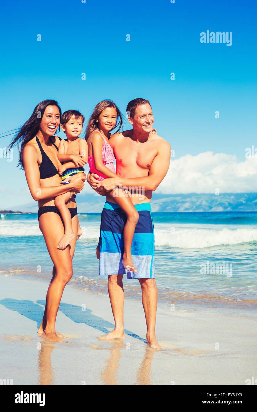 Ritratto di giovane famiglia felice avendo divertimento in spiaggia all'aperto Immagini Stock