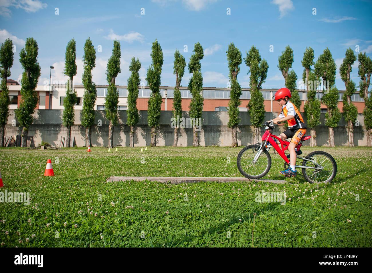 Ragazzo Equitazione Mountain bike attraverso il percorso ad ostacoli Immagini Stock