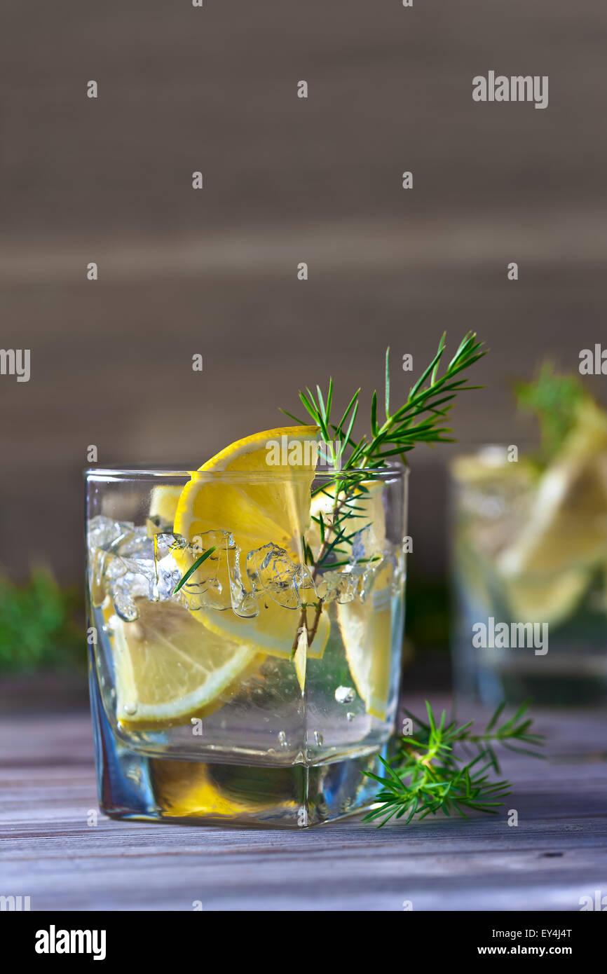 La bevanda alcolica con limone e ghiaccio su un vecchio tavolo in legno Immagini Stock