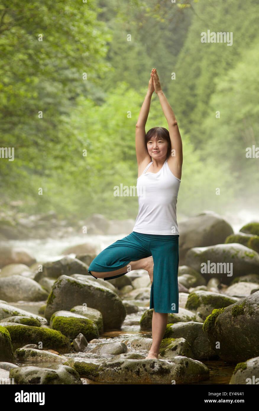 Donna asiatica di eseguire Vrksasana pongono yoga dal fiume, Lynn Valley, British Columbia, Canada Immagini Stock