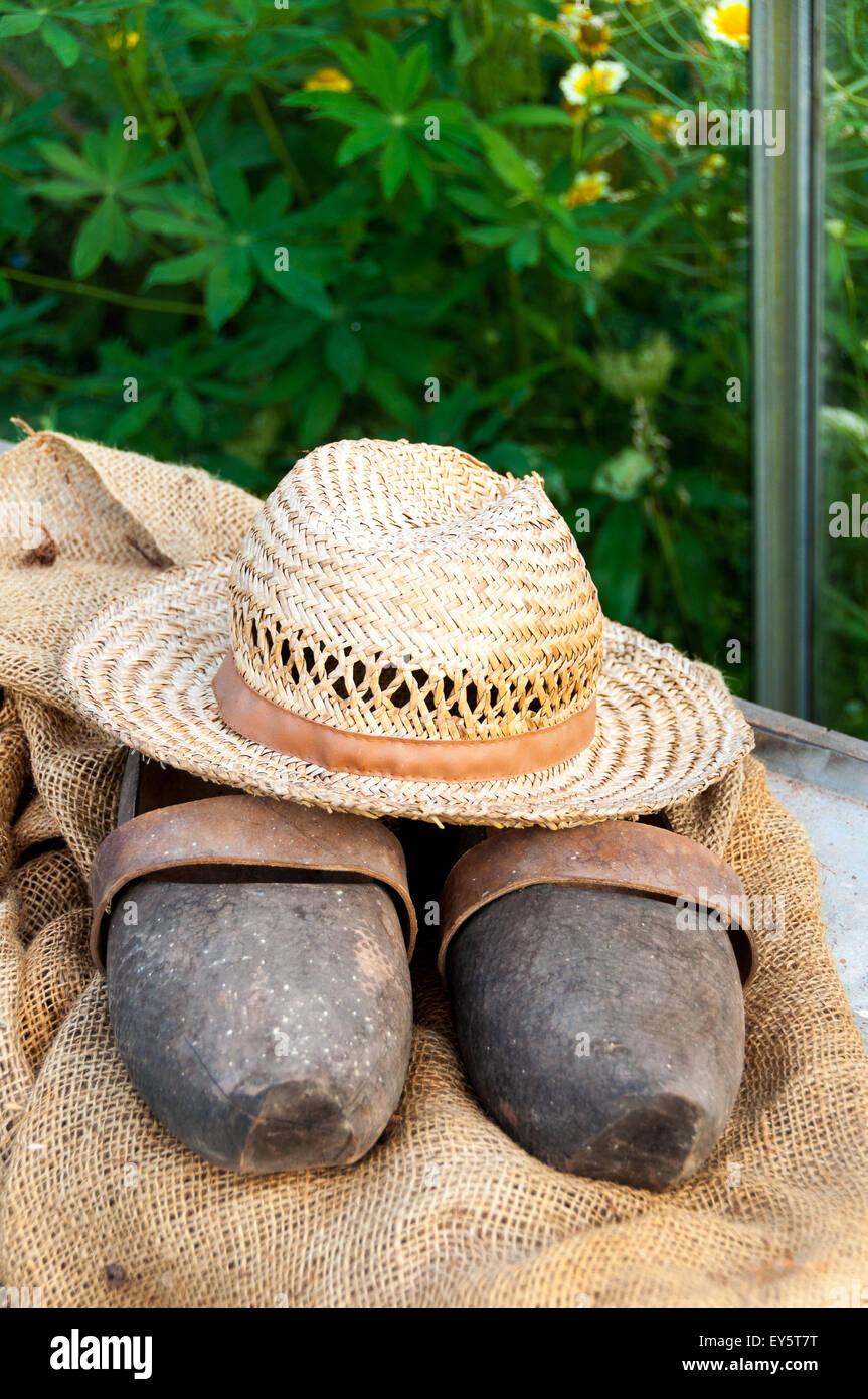 Cappello e zoccoli da giardino su hessian Immagini Stock