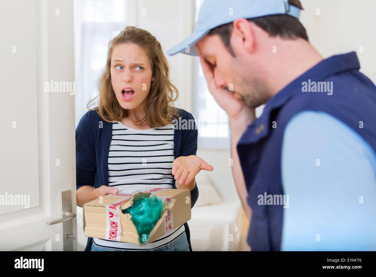 Vista di una giovane donna attraente arrabbiato contro uomo di consegna Immagini Stock
