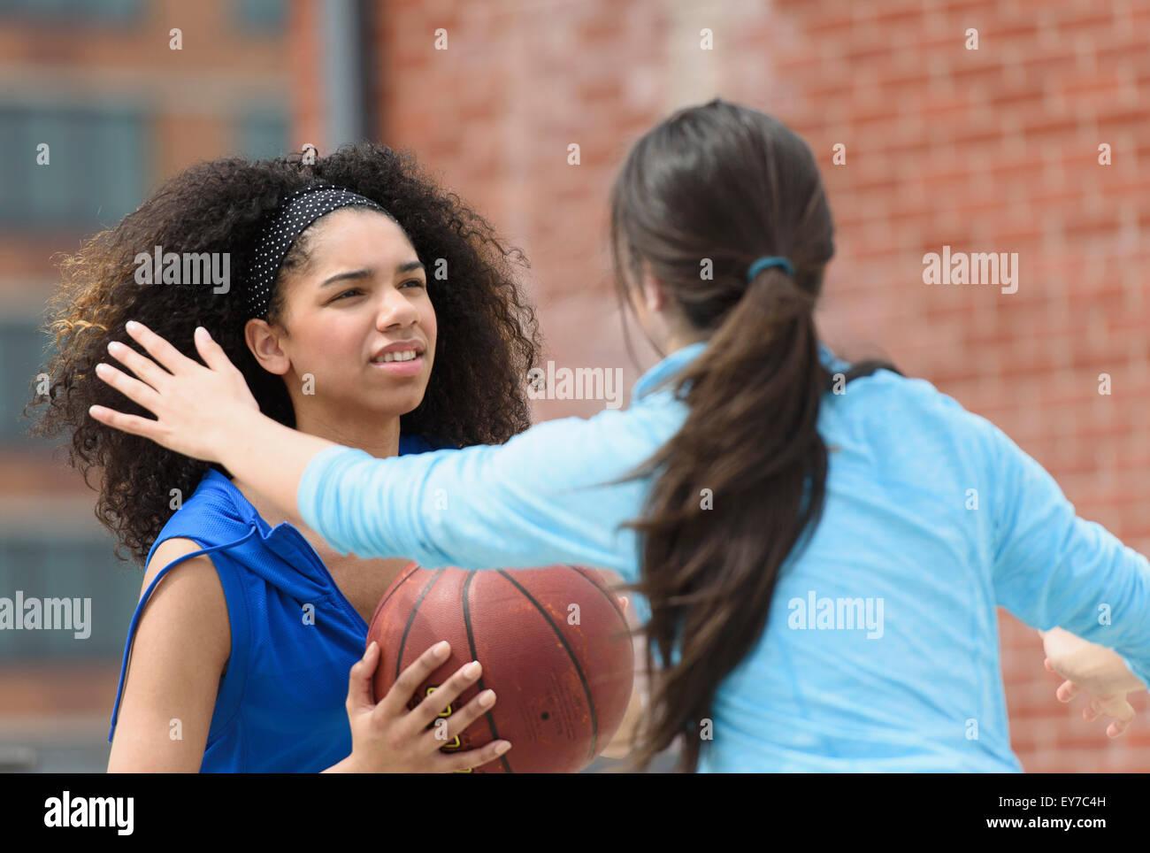 Le ragazze adolescenti (14-15, 16-17) giocare a basket Immagini Stock