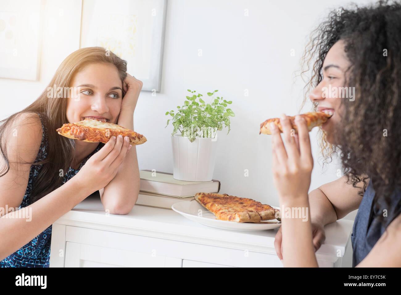 Le ragazze adolescenti (14-15, 16-17) mangiare la pizza Foto Stock