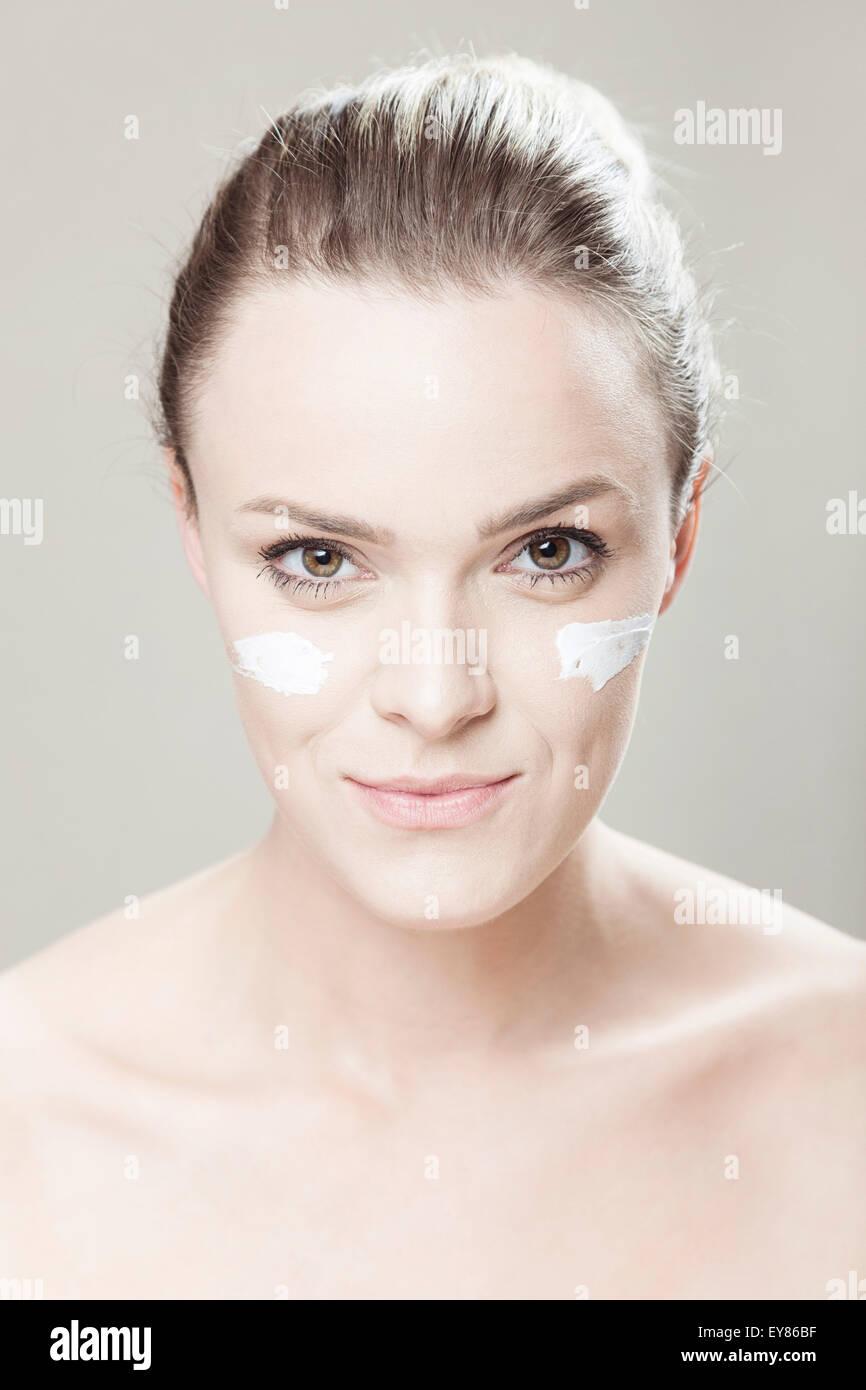 Giovane donna con striature di lozione sulla faccia Immagini Stock