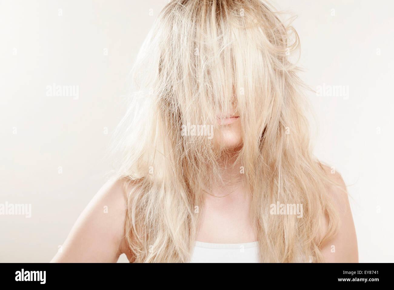 Giovane donna capelli biondi che ricopre la faccia Immagini Stock