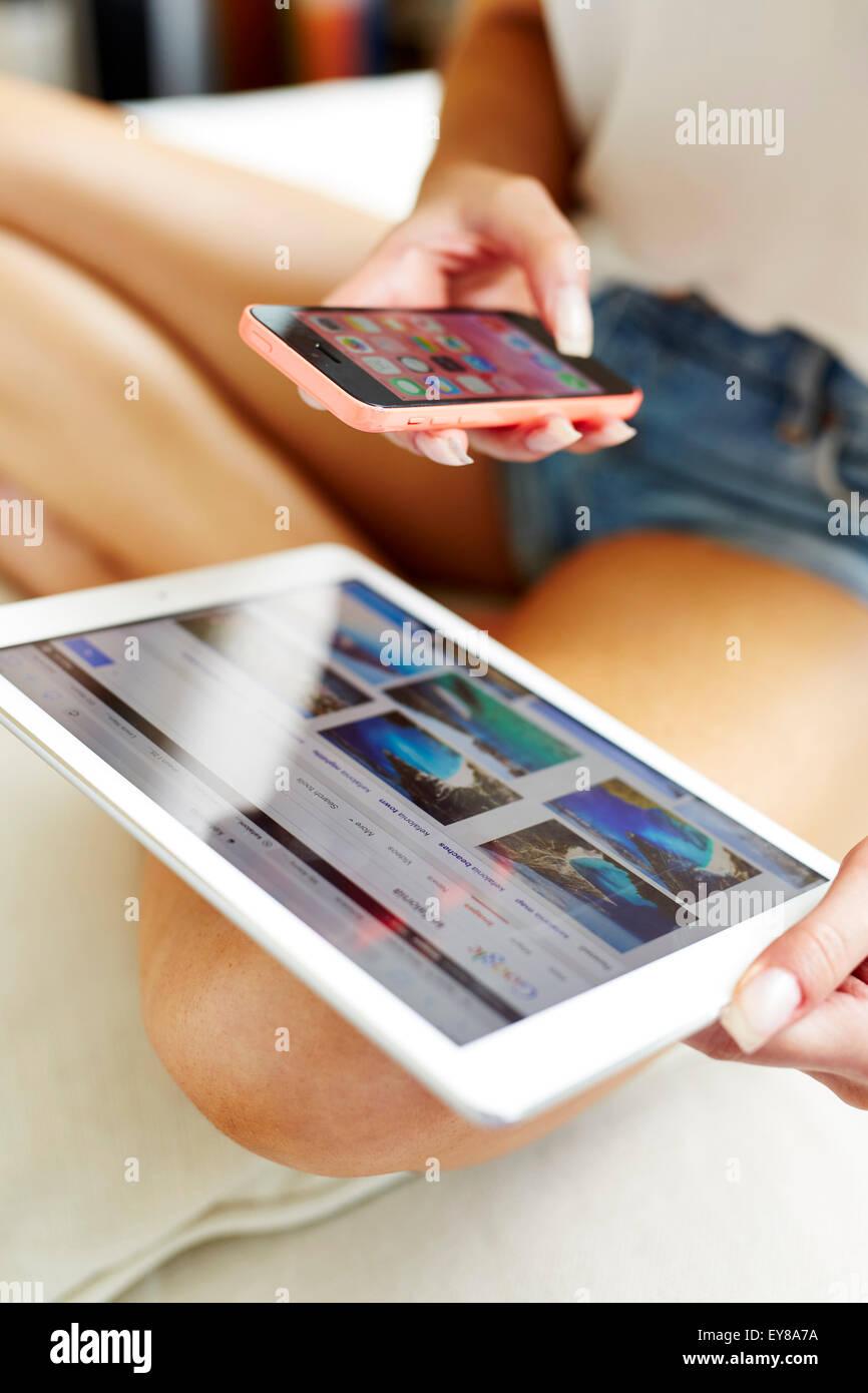 Primo piano di una ragazza utilizzando un iPad e un iPhone Immagini Stock
