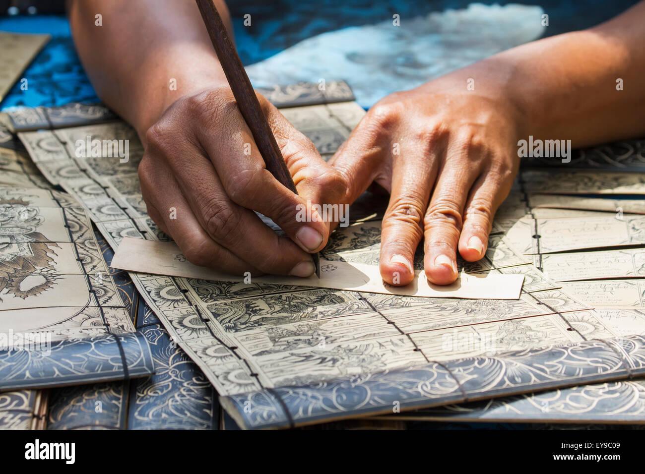 L'uomo carving gli antichi racconti in sanscrito lontar sulle foglie, Tenganan Pegringsingan, Bali, Indonesia Immagini Stock