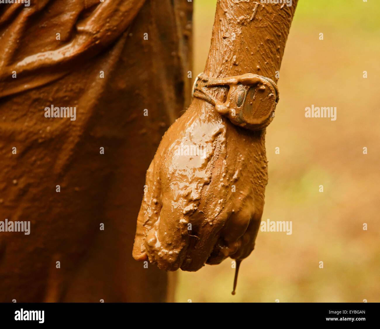 Vista dettagliata del fango-imbevuto guardare, la mano e il braccio al fango eseguire per cuore Luglio 25, 2015, Immagini Stock