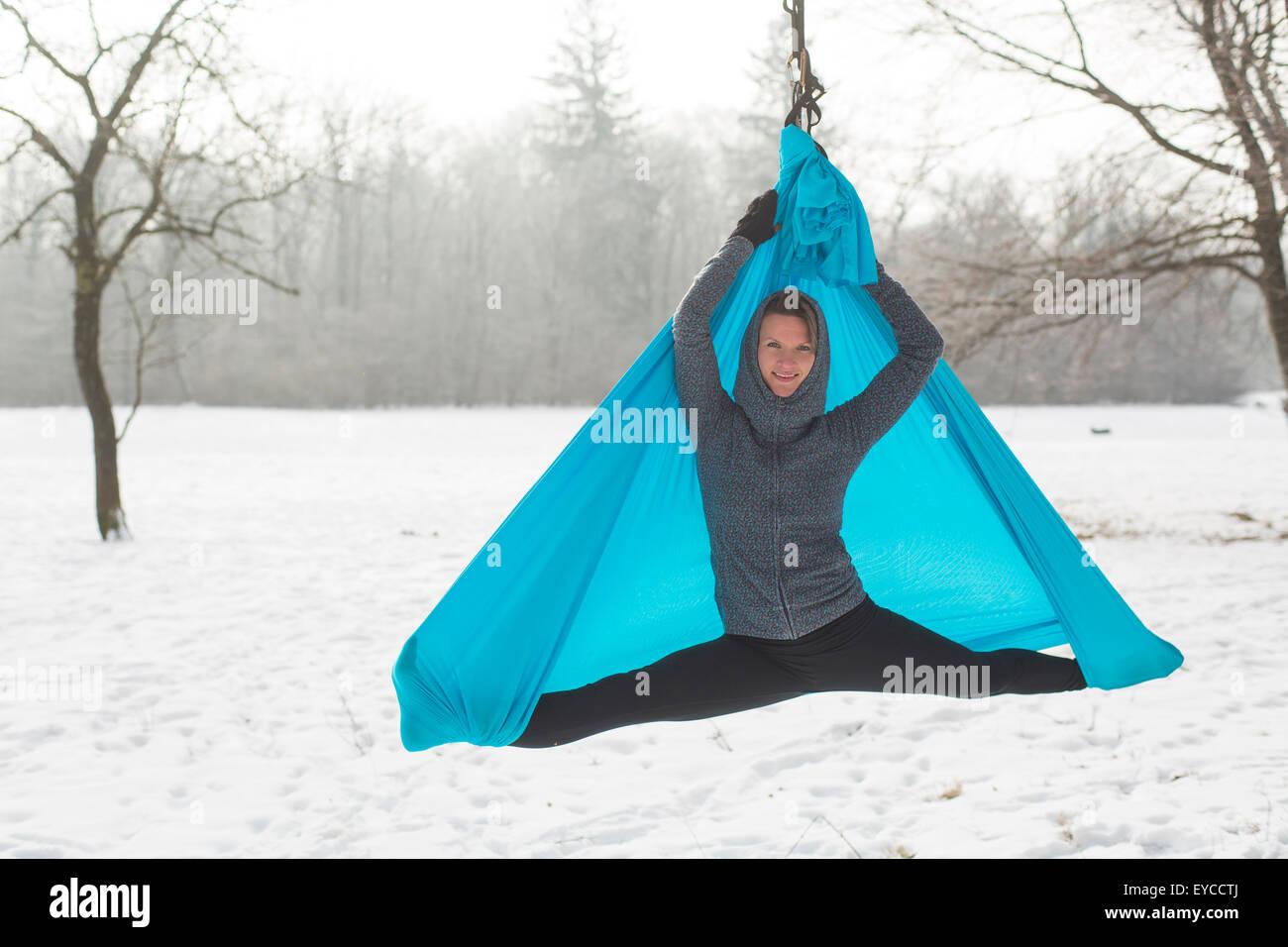 Giovane donna pratica yoga dell'antenna all'aperto Immagini Stock