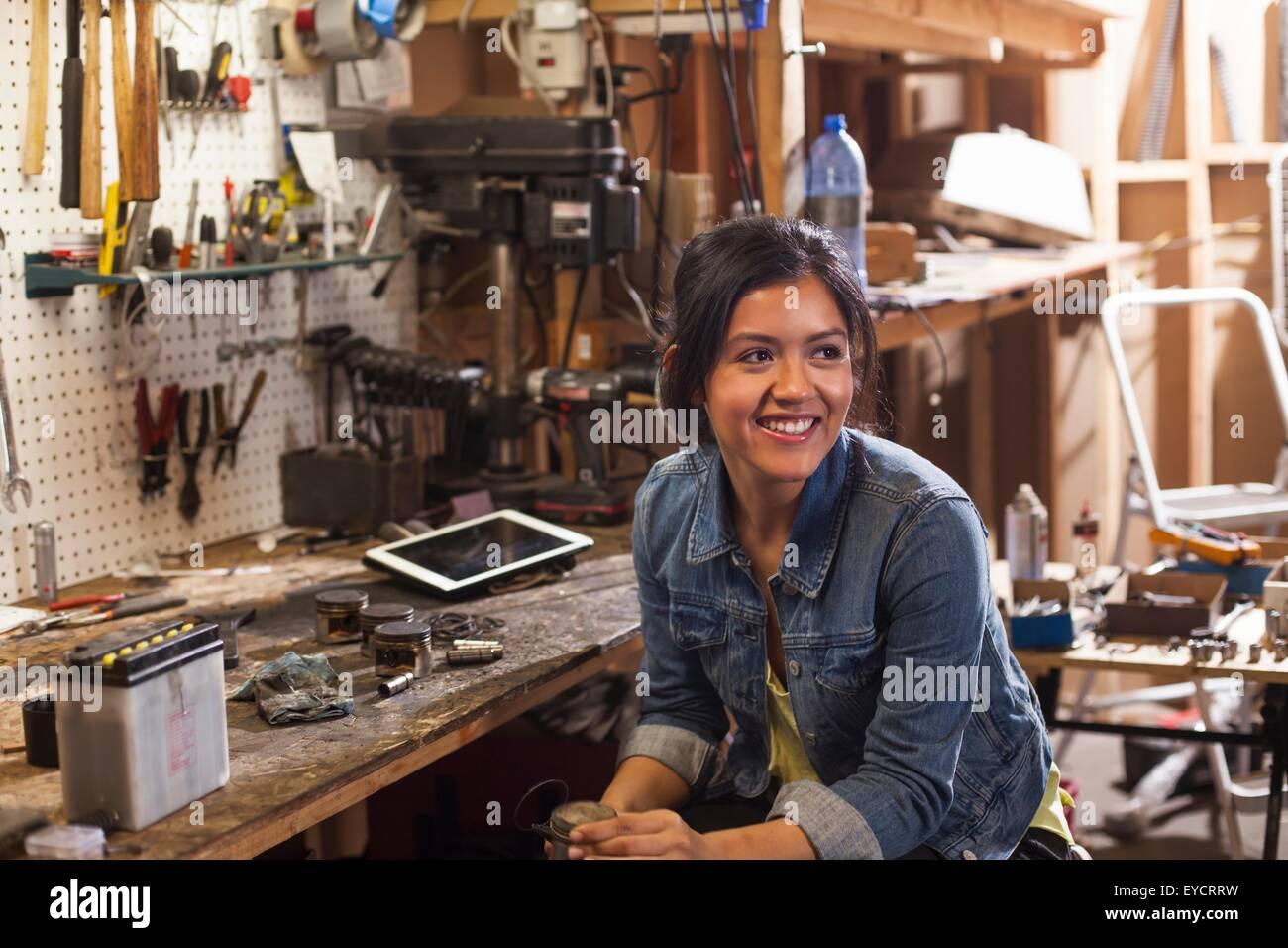 Ritratto di meccanico femmina in officina, guardando lontano, sorridente Immagini Stock