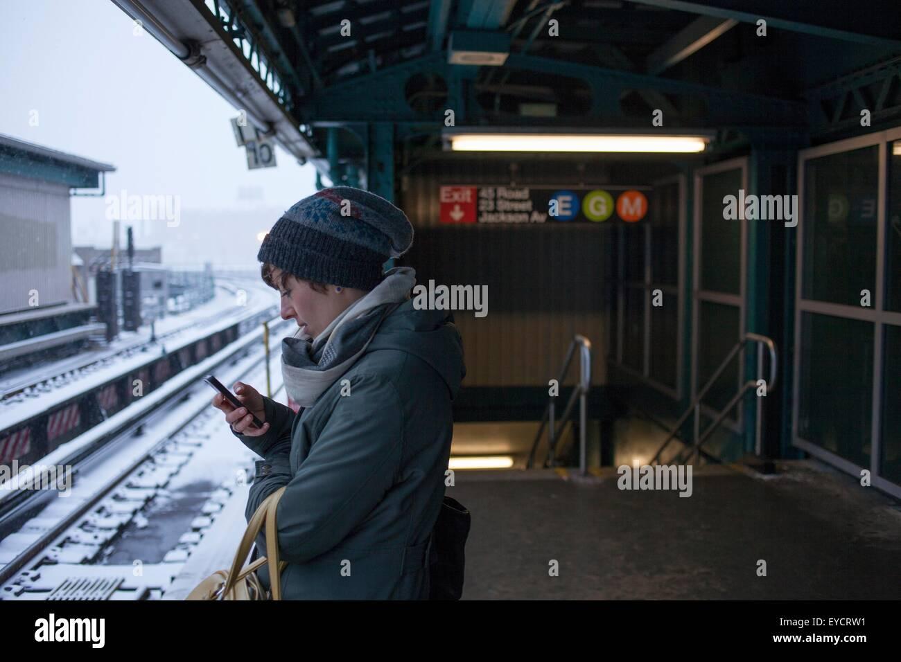 Metà donna adulta in piedi alla stazione ferroviaria tramite telefono cellulare Immagini Stock