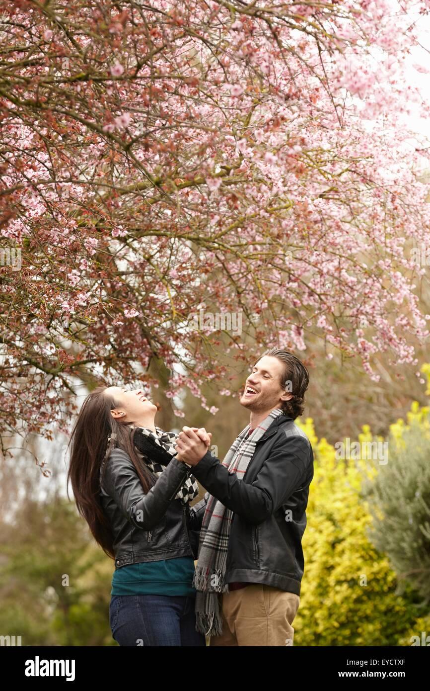 Coppia giovane ballare sotto blossom nel parco Immagini Stock